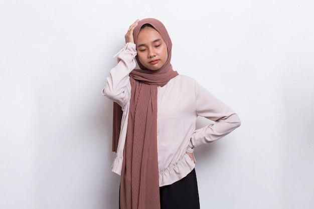 흰색 바탕에 두통이 있는 스트레스를 받는 아시아 이슬람 여성의 초상화