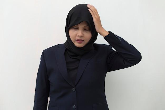頭痛の病気の女性とストレスの多い病気のイスラム教徒の女性の肖像はめまい、めまい、片頭痛、二日酔い、ヘルスケアの概念の若い大人のアジアの女性モデルに苦しんでいます