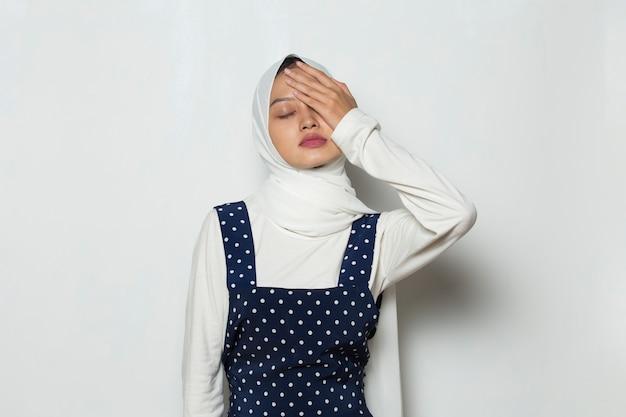 두통을 앓고 있는 스트레스를 받는 이슬람 여성의 초상화는 현기증을 앓고 있다