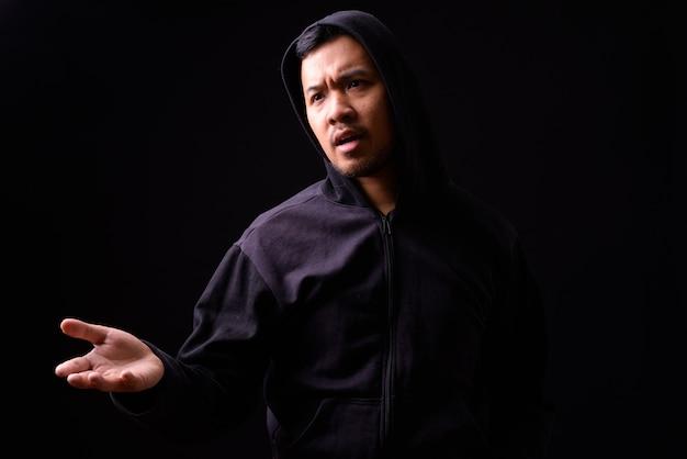 제기 손으로 불평 까마귀에 스트레스 젊은 아시아 남자의 초상화