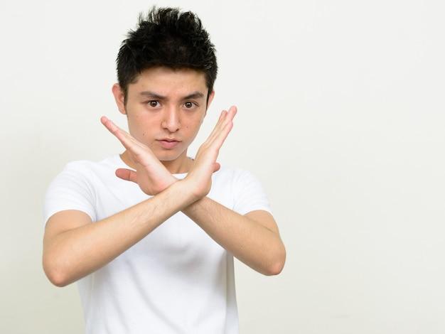 腕で停止ジェスチャーを示すストレスを受けた若いアジア人男性の肖像画
