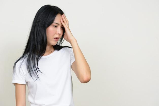 Портрет подчеркнутой молодой азиатской женщины, думающей и имеющей головную боль