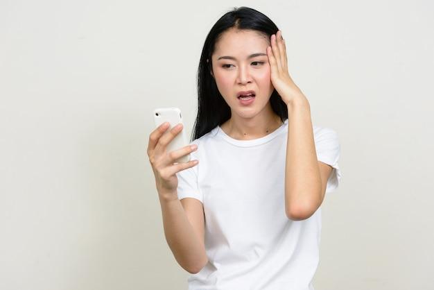 Портрет подчеркнутой молодой азиатской женщины, использующей телефон и имеющей головную боль