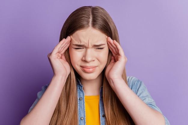 Портрет подчеркнутой молодой девушки страдает головной болью