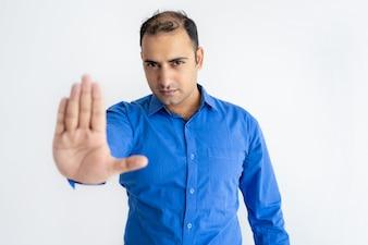 Portrait of strict mid adult businessman showing stop gesture