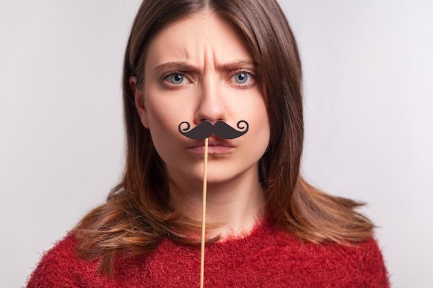 偽の巻き毛の口ひげを生やし、上司のように眉をひそめ、孤立した厳格な深刻な女の子の肖像画