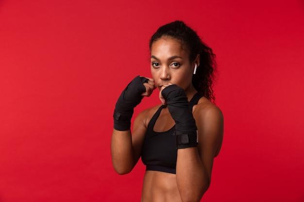 彼女の手にスポーツ包帯、赤い壁の上に分離された黒いスポーツウェアボクシングの強いアフリカ系アメリカ人女性の肖像画
