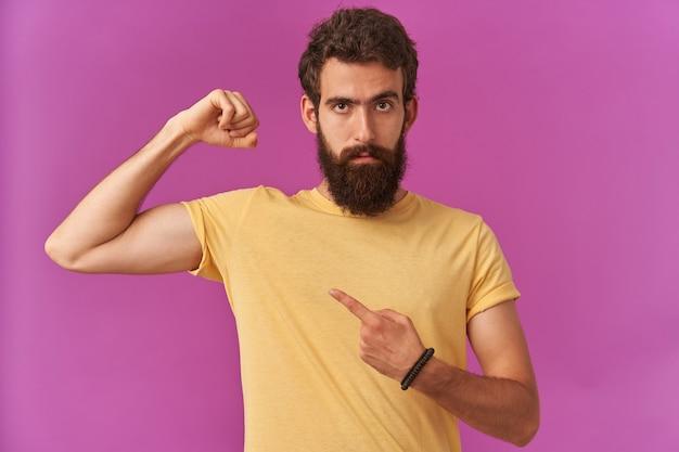 黄色いtシャツを着た茶色の目をした強いひげを生やした若い男のポートレートは、立っている上腕三頭筋に指を示し、感情に気を配り、自信を持って自信を持っている