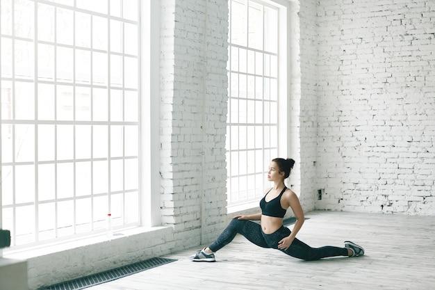 フロントスプリットの準備をして、ストレッチポーズをしている流行のスポーツ服を着た強く柔軟な若い白人スポーツウーマンの肖像画。骨盤の健康を強化するための運動をしている魅力的なフィットの女の子