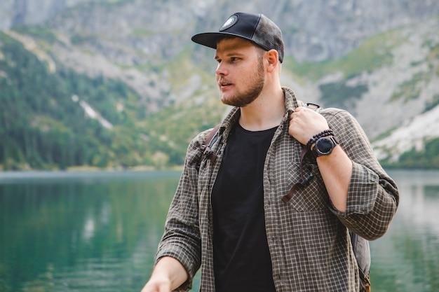山の旅行の概念の湖の前で強いハイカー男の肖像画