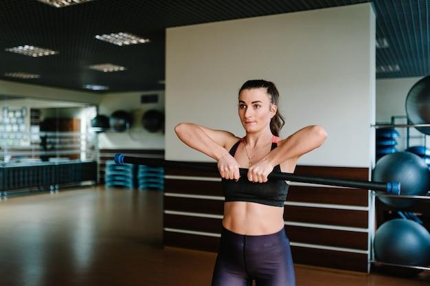 Портрет сильной спортивной женщины, делающей упражнения с боди-баром в тренажерном зале