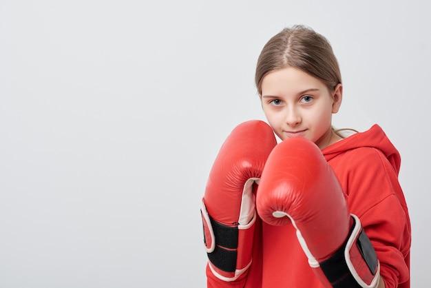 Портрет сильной девочки-подростка в боксерских перчатках, готовой к бою на тренировке