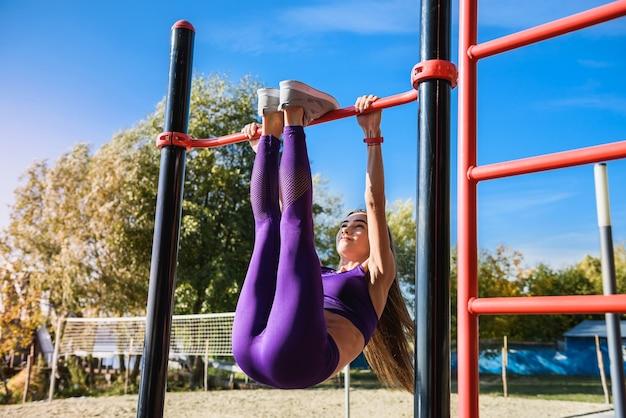 彼女の足を上にして肋木にぶら下がっているスポーツ服を着た強い若い女性の肖像画。ぶら下がっている脚を実行するフィットネス女性は屋外でレイズします