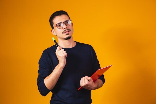 Портрет мальчика студента думая и держа тетрадь на желтом фоне.