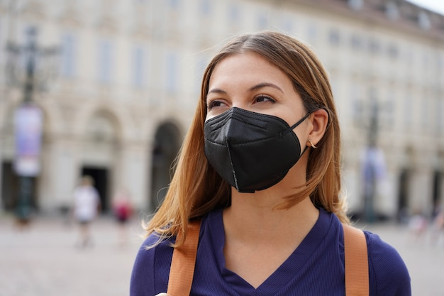街の通りを歩いている保護kn95ffp2黒いマスクを身に着けている学生の女の子の肖像画