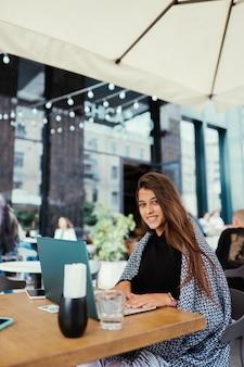 카페에 앉아있는 동안 넷북을 사용하는 학생 여자의 초상화
