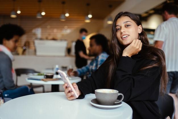 Портрет студентки с помощью смартфона, сидя в кафе