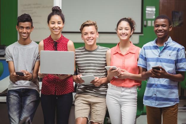 노트북, 휴대 전화, 디지털 태블릿을 들고 학생의 초상화