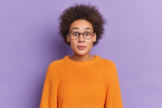 オレンジ色のセーターを着た眼鏡を通して見つめる唖然とした巻き毛のミレニアル世代の少女の肖像画は、衝撃的なニュースに反応します。