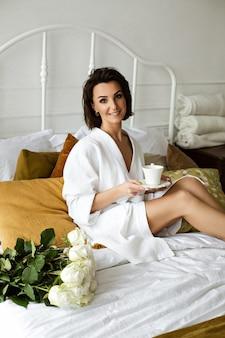 흰색 목욕 가운을 입은 멋진 브루네트의 초상화는 호텔 침대에서 손에 커피 한 잔과 그녀 옆에 장미 꽃다발을 들고 아침을 즐기고 있습니다.