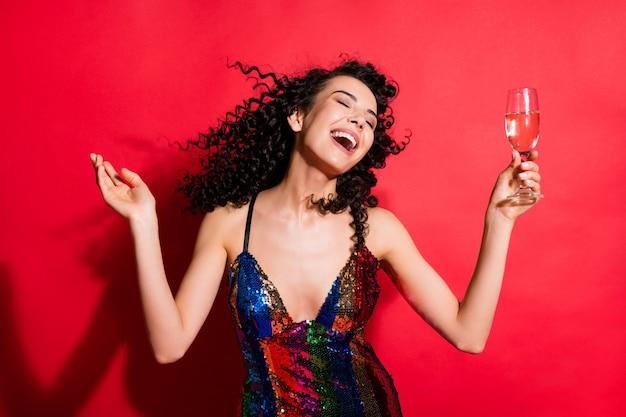 鮮やかな赤い色の背景に分離された楽しみを持ってワインダンスを飲む見事な夢のような陽気なウェーブのかかった髪の少女の肖像画