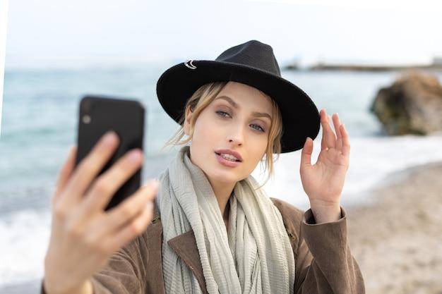 スタイリッシュな帽子をかぶったまま携帯電話を使って自分撮りをしている見事な女性モデルの肖像画
