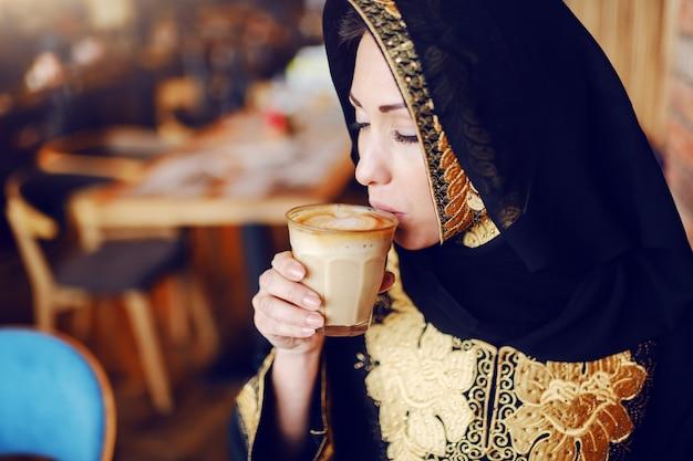 カフェに座ってコーヒーを飲む伝統的な摩耗で見事なイスラム教徒の女性の肖像画。