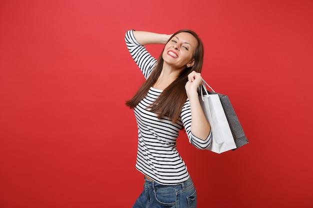 줄무늬 옷을 입은 멋진 젊은 여성의 초상화는 붉은 벽 배경에서 격리된 쇼핑 후 구매한 패키지 가방을 들고 있습니다. 사람들은 진심 어린 감정, 라이프 스타일 개념입니다. 복사 공간을 비웃습니다.