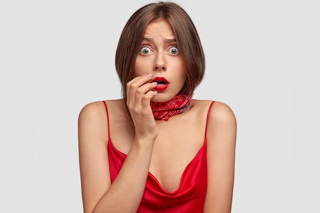 Портрет ошеломленной брюнетки молодой женщины позирует у белой стены