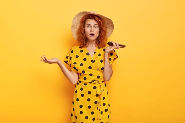 Портрет ошеломленной девушки-модели держит мобильный телефон, потрясенный парень не звонит