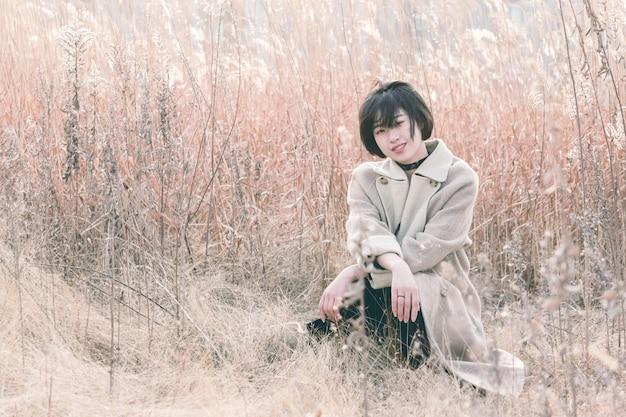 リードフィールドの中に座っているスタイルの女性の肖像