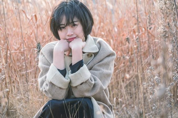 リードフィールドの中に座っているスタイルの女性の肖像 Premium写真