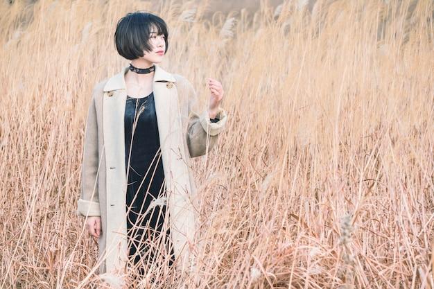 リードフィールドの中に立っているスタイルの女性の肖像 Premium写真