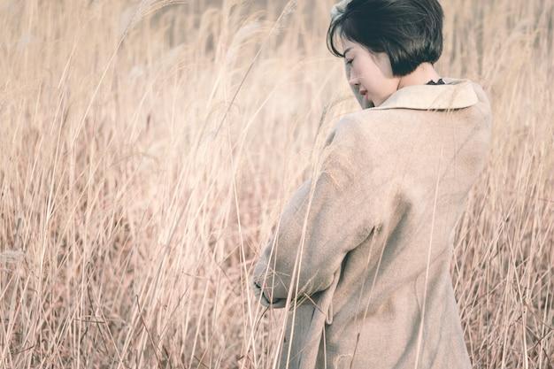 リードフィールドの中に立っているスタイルの女性の肖像