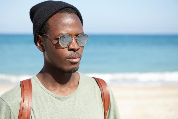 ビーチでスタイリッシュなアフリカ系アメリカ人の男の肖像
