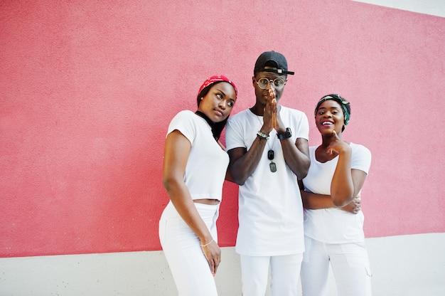 세련 된 아프리카 계 미국인 남자 두 여자와 손을기도의 초상화 분홍색 벽에 흰 옷을 입고. 젊은 흑인의 스트리트 패션.