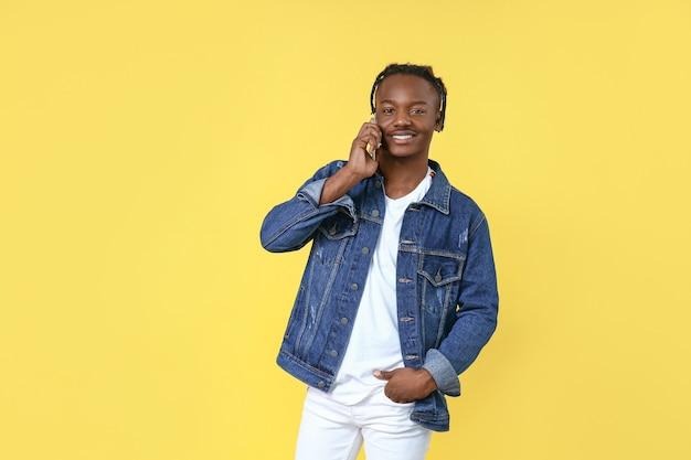 黄色の携帯電話で話しているスタイリッシュなアフリカ系アメリカ人男性の肖像画