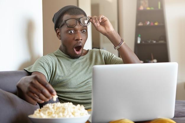Портрет стильного афро-американского мужчины с ноутбуком дома