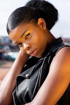 Портрет стильной африканской женщины в кожаном жилете на открытом воздухе