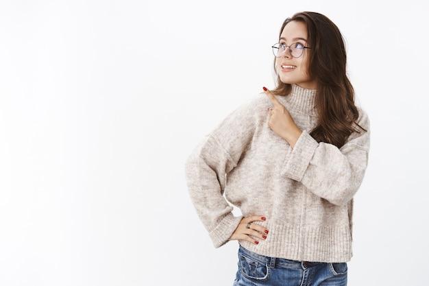 안경과 스웨터를 입은 세련되고 자신감 있는 여성 프리랜서의 초상화는 흥미로운 카피 공간을 관찰하며 기쁘게 흥미로운 미소를 지으며 왼쪽 상단 모서리를 가리키고 있습니다.