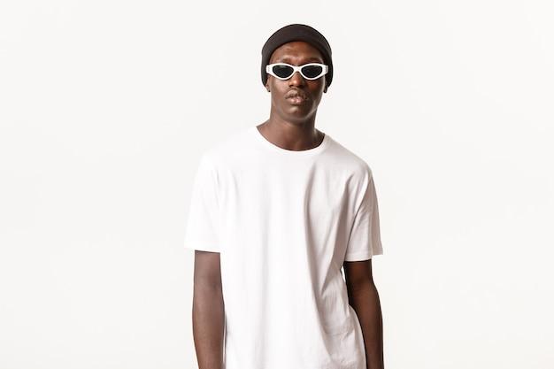 Портрет стильного и крутого афро-американского молодого парня в шапочке и солнцезащитных очках