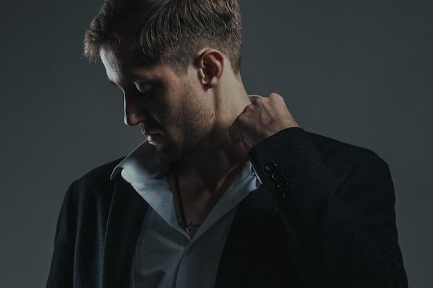 彼の襟を調整するスタイリッシュでセクシーな若いひげを生やした実業家の肖像画。