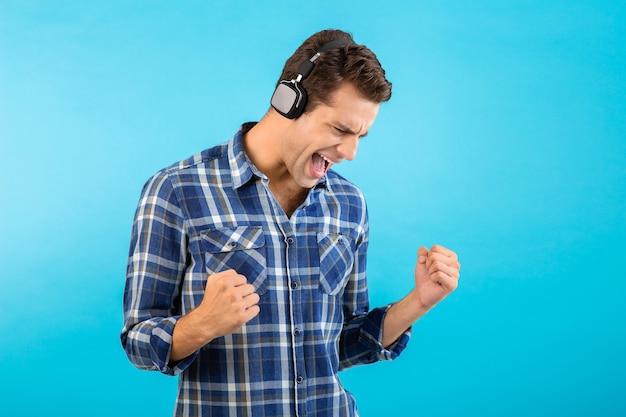 チェッカーシャツを着て青い背景に分離された楽しいモダンなスタイルの幸せな感情的な気分を持っているワイヤレスヘッドフォンで音楽を聴いているスタイリッシュで魅力的なハンサムな若い男の肖像画
