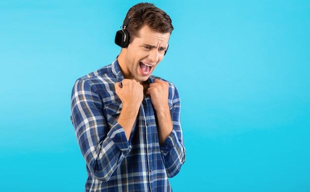 Портрет стильного привлекательного красивого молодого человека, слушающего музыку на беспроводных наушниках, веселого современного стиля, счастливого эмоционального настроения, изолированного на синем фоне, в клетчатой рубашке