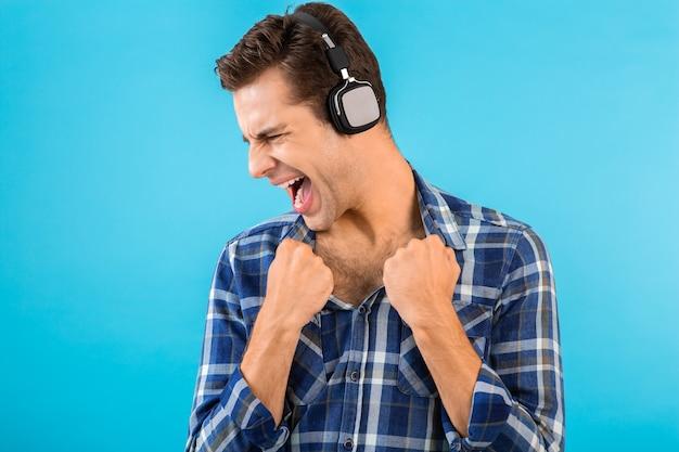 モダンなスタイルの幸せな感情的な気分を楽しんでいるワイヤレス ヘッドフォンで音楽を聴くスタイリッシュな魅力的なハンサムな若い男の肖像