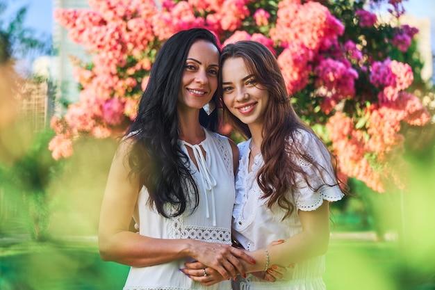 Портрет стильной привлекательной улыбающейся радостной счастливой матери с дочерью, обнимающейся и смотрящей в камеру вместе в парке на открытом воздухе