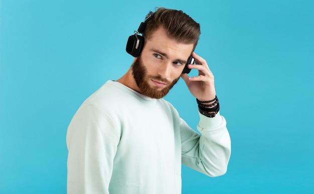 ワイヤレスヘッドフォンで音楽を聴いているスタイリッシュで魅力的な若いひげを生やした男の肖像画青い背景で隔離のモダンなスタイルの自信を持って気分 無料写真