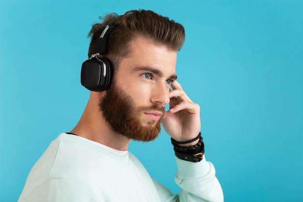 Портрет стильного привлекательного молодого бородатого мужчины, слушающего музыку на беспроводных наушниках в современном стиле, уверенное настроение, изолированное на синем фоне