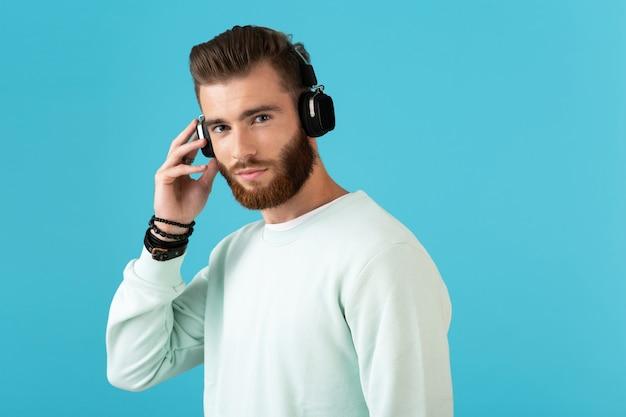 Портрет стильного привлекательного молодого бородатого мужчины, слушающего музыку на беспроводных наушниках в современном стиле, уверенное настроение