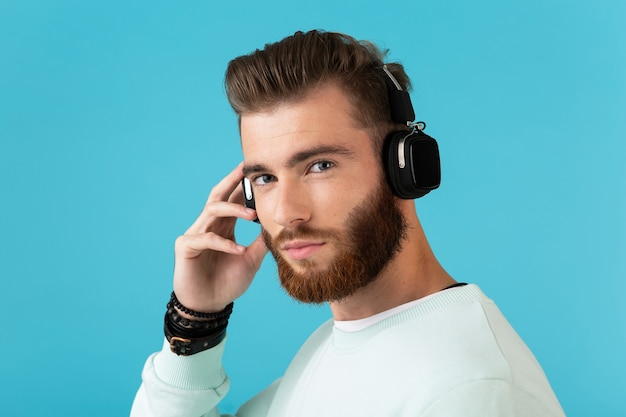 ワイヤレス ヘッドフォン モダンなスタイルの自信に満ちた気分で音楽を聴いているスタイリッシュな魅力的な若いひげを生やした男の肖像